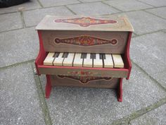 "Antique European Toy Piano of wood and cardboard with metal ""xylophone"" or Glockenspiel sound plates."