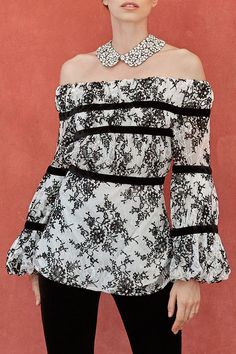 56238c1029437 The SEMIRA is a white lace blouse with black contrasting velvet floral  patterns and is adorned