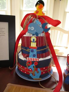 Nautical inspired Diaper Cake for a recent baby shower! Ribbon and fabric, rubber ducky and diapers from Walmart, Jute twine and wooden decor from hobby lobby.