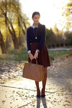 Shop this look on Lookastic:  http://lookastic.com/women/looks/dress-shirt-and-crew-neck-sweater-and-mini-skirt-and-tote-bag-and-pumps-and-pendant/3815  — Blue Print Dress Shirt  — Navy Crew-neck Sweater  — Burgundy Pleated Mini Skirt  — Brown Leather Tote Bag  — Navy Suede Pumps  — Gold Pendant