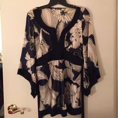 Beautiful kimono style top I got this as a gift. Tag is not on it but the little plastic piece is. Mandee brand size L. Feels like a silky material but it's polyester. Cute sleeves (see photo) and ties in the back. Navy blue, black, and white detailing. mandee Tops