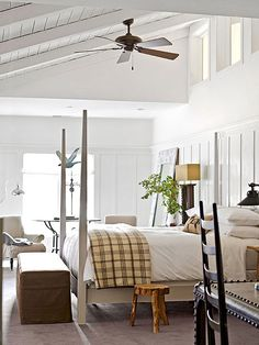 Farmhouse Guest Bedroom : Paneled walls and a beaded-board ceiling create a cozy farmhouse-inspired look. White paneling that extends almost all the way up the wall draws attention to the room's unique sloped ceiling. Meanwhile, thick planks and beams add subtle texture to the ceiling, which prevent the tall room from looking stark and cold. White modernizes this bedroom but quaint accents return the room to its farmhouse roots, creating a look that blends both sleek and rustic.