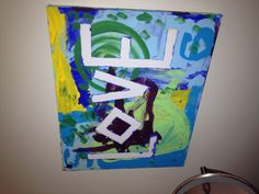Taped the letters on a blank canvas and then let the kids paint over it. Once it dried, I pulled off the tape.