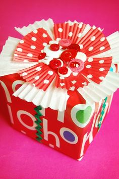 so cute!  different size muffin/cupcake wrappers cut to look like flower as base of cute decor on wrapped gift