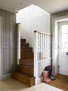 Wellington boots on doormat in staircase hallway of Hampshire farmhouse  England  UK