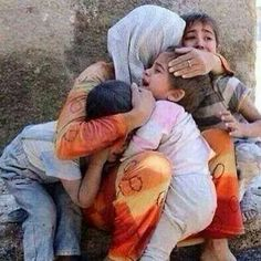 A Mother tries to comfort and protect her children during Israeli bombing of Gaza.