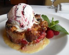 "Raspberry & Dark Chocolate Donut ""Bread"" Pudding -- house made yeast donuts, tossed dark chocolate, fresh raspberries and toasted Marcona almonds. Soaked in cinnamon, orange zest and nutmeg infused creme brulee batter. Roasted golden, served warm to order with Chambord whipped cream icing, fresh raspberries and white chocolate, raspberry chocolate chip ice cream. #johnhowiesteak #dessert"