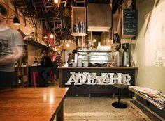 En Melbourne encontramos este original café.    Un local pequeño en el que se dejó las paredes oportunamente inacabadas. Mobiliario dispar, cajones reciclados sobre la barra y sobretodo un peculiar techo poblado de sillas viejas colgantes.