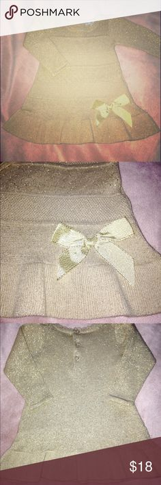 Beautiful Gold, Sparkly Sweater Dress ✨ Beautiful Gold, Sparkly Sweater Dress ✨ Could be worn with tights or leggings. My daughter wore it ONCE with tights & boots. It is gold with a little bit of sparkle all throughout the material. A ruffle on the bottom with a gold ribbon bow 🎀 Also, a little bit of a ruffle around the neck. There are three buttons that go up the back. LIKE NEW 🎉 GREAT CONDITION 🎉 Zip Zap Dresses Formal