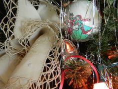 Very Simple Christmas Tree Decor:  antique spoons tied with red ribbon, antique napkins with lace, icicles,  ornaments and large colored lights.