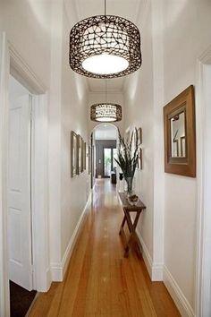 Suspensions design et cadres bois dans une déco couloir