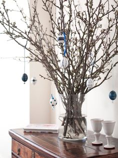 Gwyneth's Easter tree. White English blossom branches in a glass vase. Handmade egg ornaments.