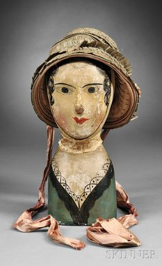 Papier-mache Milliner's Model with a Silk Hat, probably France, early 19th century bust-length model with painted facial features, hair, and dress bodice, applied kidskin cap with padded back, wearing a green and white woven windowpane pattern silk hat with wire framework, lined with pink silk and tied with pink silk ribbons, Skinner.