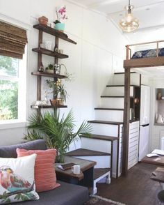 The two-toned stairs with wooden treads lead to a bedroom loft. Tucked in the corner of the home is a full-size bath with standing shower, built-in medicine cabinet, toilet,and cabinets.