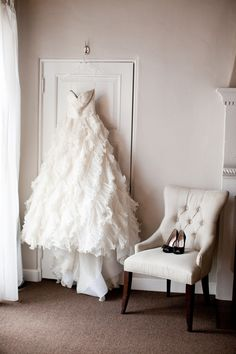 A stunning gown hanging and pretty shoes on a tufted chair.
