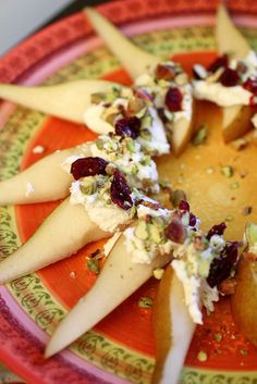 Easy appetizer: pear slices with goat cheese, craisins, and pistachios