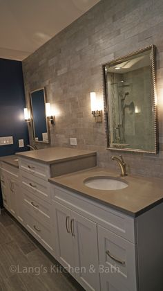 This transitional bathroom design combines the comfort of a traditional style with the sleek lines of a contemporary design.  The large glass shower enclosure incorporates many features including a custom shower niche with built in storage and a shower seat, a mosaic tile detail, a rainfall and handheld showerhead, and wood plank tile shower floor.  A freestanding tub sits beside the shower.  The multi-level vanity with polished nickel hardware is complemented by the mirrors and light…