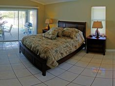 "Master bedroom with king size bed, 26"" tv, ensuite bathroom, walk-in closet and patio doors that lead into pool area."