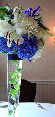 Amanda Garzieri - Wedding Centerpieces - 24 inch trumpet vase with some arrangement on top and maybe vase filler instead of water