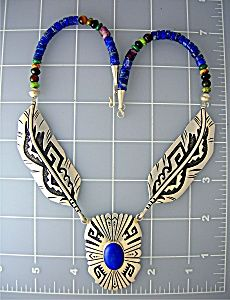 Tommy Singer Beautiful Wearable Art necklace. The necklace is 19 inches end to end and the Large center Sterling Silver Lapis Pendant. Feathers have Black Oxydisation. Center pendant is 2 inches long and 1 inch wide. There is a large Lapis Cabochon in the center. The Feathers either side are each 3 1/2 inches. either side of the feathers are Tommy Singer Signature Beads in Lapis Onyx Spiny Oyster and Turquoise. ALL 3 of the Silver pieces are signed T Singer Sterling.