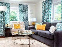 Gri koltuklar, renkli kırlentler ve turkuaz desenli perde