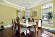 Yellow and white dining room design with wood floor, wood chairs and white dining table that seats eight people.