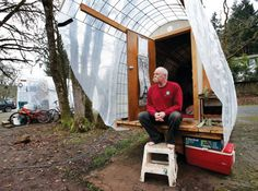 Mark Hubbell sits on the porch of his Conestoga Hut