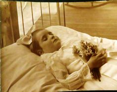 Young girl posed on a bed with a bouquet flowers in her hands.