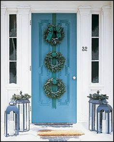 a Blue Christmas door with three wreaths and lanterns