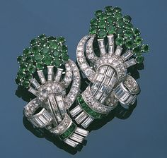 An emerald and diamond double clip brooch, circa 1935  Designed as two stylised foliate sprays, composed of channel-set baguette-cut diamond stems and circular-cut emerald blooms, within a surround of scrolling baguette and brilliant-cut diamond ribbons and calibré-cut emerald ties, diamonds approximately 4.10 carats total, one diamond deficient, length of each brooch 5.2cm and 4.8cm