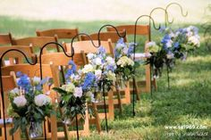 Mason jars were equipped with wire hangers, filled with small floral bouquets, and hung from shepherds hooks at the end of each row of chairs.