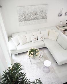 Suuri huonekorkeus antaa ilmavuutta olohuoneen vaaleaan sohvanurkkaukseen. Huomaa myös kaunis taulu seinällä sekä Kartell Stone jakkara ja valkoinen Hay tarjotinpöytä.