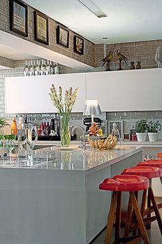 O revestimento cerâmico retangular e a bancada de Silestone dão modernidade à cozinha. Os vasos com temperos são xodós do morador André Almada, que gostaria de ter mais plantas. Objetos bem-humorados, como a fruteira de bananas, completam a decoração