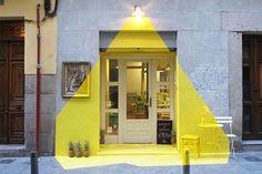"""""""Fos""""  Em Madrid, na Espanha, o restaurante vegetariano Rayen inovou na hora de pintar sua fachada e acabou fazendo um tremendo sucesso, conforme falamos aqui. A instalação, feita por Eleni Karpatsi, Susana Piquer e Julio Calma, foi feita com tinta adesiva amarela, alguns itens de decoração e uma luminária, criando a ilusão de um foco de luz sobre a porta do local. Simples e muito inteligente."""