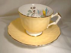 Aynsley 29 yellow tea cup and saucer with blackberries from the 1970s. This English bone china 2-3/4 in height teacup and matching 5-3/4 saucer is in the yellow variant with blackberries and a floral arrangement inside the cup. It has a petal and leaf relief shape with a scalloped edge and gold trim and it would make a lovely display as well as a very nice teacup for your tea or coffee. It is in excellent original condition with no chips, cracks, dents, bends, corrosion, losses, dam...