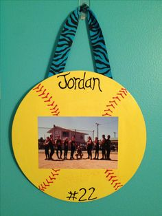 Wooden circle shaped board painted like a softball and I added girls names and numbers on it with a pic in the middle. Easy and cheap gift for your softball team.