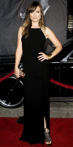 Olivia Wilde in a Yigal Azrouel silk crepe gown accented with gold bangles from BaubleBar and Ippolita, Lucifer Vir Honestus earrings, an animal-print Alexander McQueen clutch and strappy sandals.