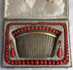 Fazetted coral necklace, pair of earrings, and hair comb, in original red leather box. Probably Italian ca 1780-1800.  The paired red jewelries represent health and luck during this period.