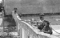The September 9, 1961 file photo shows East-German policemen in work dress as they remove barbed wire from a brick wall while other policemen in background are raising the wall to 15 feet at the border between the French and Russian sector at Bernauer Strasse in Berlin. (Photo by Edwin Reichert/AP Photo)
