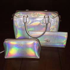 COACH HOLOGRAM SET Coach silver hologram purse/wallet/makeup pouch, only set available! This style is so unique & perfect for any season, purse is smaller with handles and crossbody strap, wallet has button closure & plenty of card slots, makeup bag could even be used in the purse as an organizer. Bag 10Lx7Hx5D; wallet 8Lx4H; pouch 7Lx4Hx3D. * I would consider separating if requested * NWT directly from store! Coach Bags