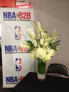 A tall cylinder vase featuring white calla lilies, white hydrangea and white stock.  To view our entire selection, please visit us at www.starflor.com or to discuss decor for an upcoming event please call us at 800.520.8999   #flowers #events #decor #nba