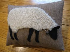 Wonderful, realistic grazing sheep made from a woolly plush fabric. He has black wool felt legs, face and ear that sticks up off the pillow. Ive added a rusty bell around his neck on a piece of rustic aged string. The design is stitched onto a background of light brown wool.  This is my own design and is drawn, cut and stitched by hand. It is another of several different sheep pillows that I make. It measures 9x12 and is stuffed with polyester fiberfil. Comes from a pet and smoke free home…