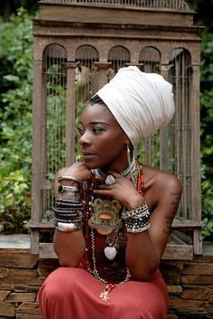 Regal head wrap on a beautiful black woman. I love her jewelry too!