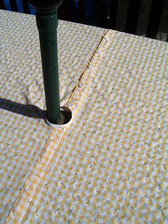Tablecloth for picnic table that has umbrella.