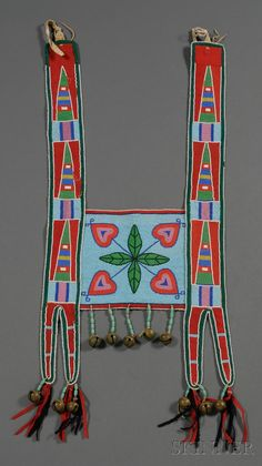 Plains Beaded Cloth Horse Collar, Crow, c. first quarter 20th century, the straps with classic geometric designs on trade cloth, with floral beaded panel on a light blue ground, trade bead, brass bells, and red and blue trade cloth strips hang from the bottom, canvas backed.