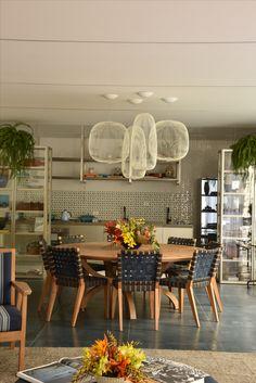 Imagem da mesa redonda que integra a casa de praia Decortiles, projeto de Marina Linhares para a Casa Cor 2017. Tanto ela quanto as cadeiras são da Etel Interiores. Os pendentes são Lumini, e, no fundo, os armários são Ornare.
