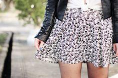 Look com blusa branca saia rodada estampada com caveiras jaqueta de couro meia calça poá e sapatilha vermelha