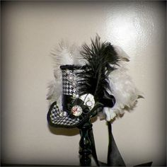 Mini Top Hat Fascinator Mad Hatter Red Black is trimmed withwhite and black feathers this little one of a kind hat is a must have for everyone. Many upcycled items are always used to create this tiny little work of art, trimmed with tiny roses, a clock , satin ribbon and a handmade hat pin.   All hats are one of a kind, I never make two the same, this one is 6 inches wide and 4 inches tall. It is held on your head with a elastic band, this makes it easy to wear on either side of your head or…