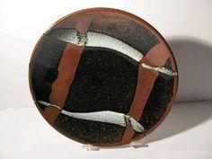 Shoji Hamada (1894-1978): a studio pottery dish, tenmoku ground with trailed design of kaki and white slip.
