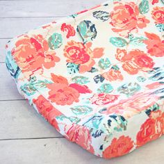 This floral changing pad cover from Caden Lane is the perfect color combination of coral and navy. This changing pad cover stand alone!